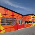 Frontansicht der Halle Malerbetrieb Rebl mit Klecksen in den Firmenfarben