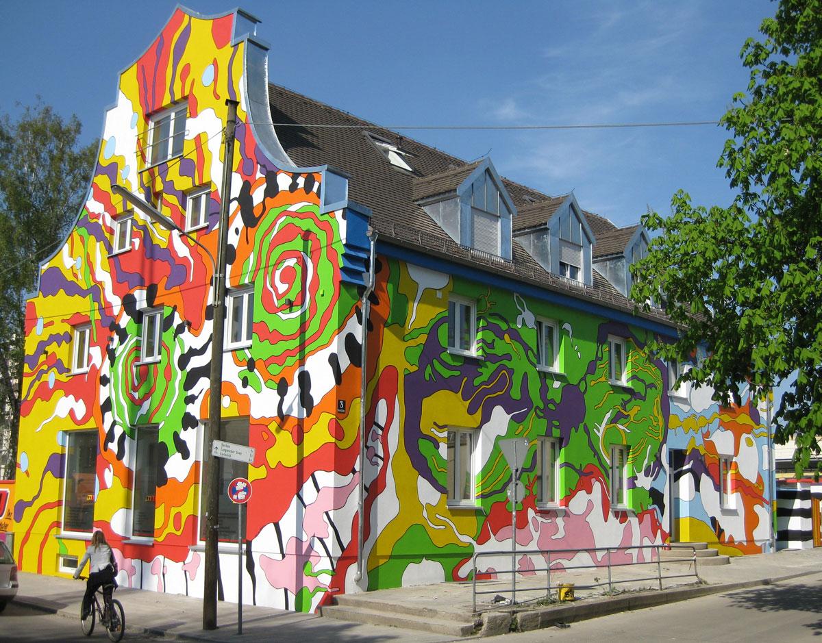 Ansicht Straße/ Örtlplatz mit zwei überdimensionalen, abstrakten Gesichtern